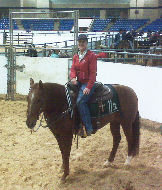 A woman rides a horse belonging to Cutting Horse trainer Bill Riddle. The horse has a Branded Brown Cow Saddle Blanket