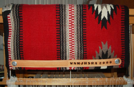 a hand-made Brown Cow Saddle Blanket with hand-tooled wear-leathers that have the award written into the leather