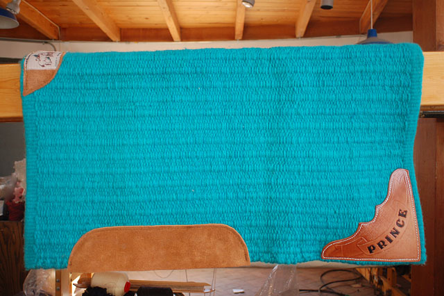 Hand-woven turquoise saddle blanket with hand tooled leather name plate.